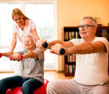 nurse helps senior to doing exercise