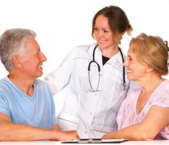 nurse and senior couple smiling